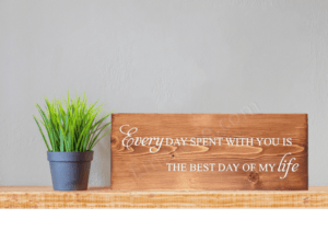 Every Day Spent With You Is The Best Day of My Life Wood Sign on a wood shelf with a small plant beside the sign